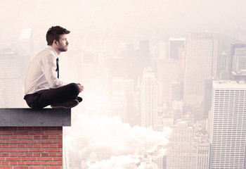 Office worker sitting on rooftop in city