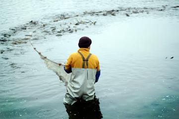 Obraz Rybak ciągnie sieć pełną ryb - fototapety do salonu