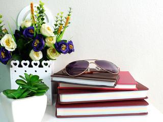 stack of notebook with artificial of plant and sunglasses