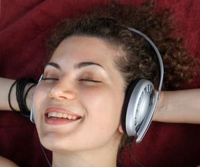 Ragazza che ascolta musica con cuffia sdraiata sul parato