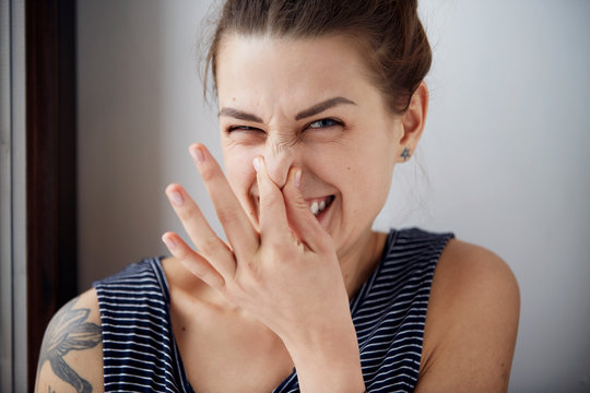 Female gesture smells bad. Headshot woman pinches nose with fingers hands looks with disgust something stinks bad smell situation. Human face expression body language reaction.