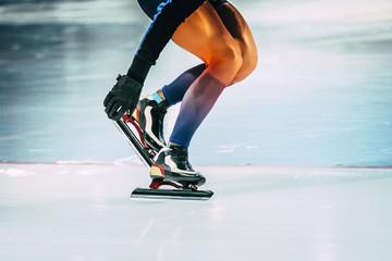closeup girl athlete speed skating shoveling snow with skate blades