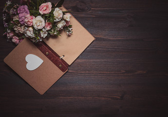 Vintage books and romantic flowers on a wooden background