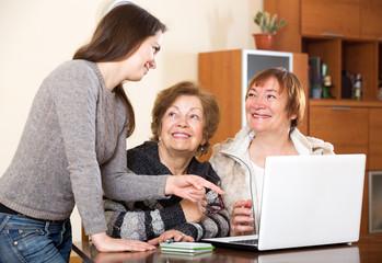 Cheerful girl helping senior women