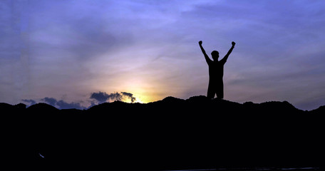 silhouette of man show arm up for achievements successful and celebrating success with sunrise