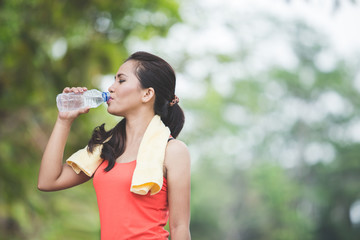 Young asian woman drinking water after doing excercise outdoor i