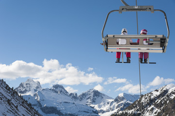 Chairlift full of skiers at a ski resort with snowy mountains on background