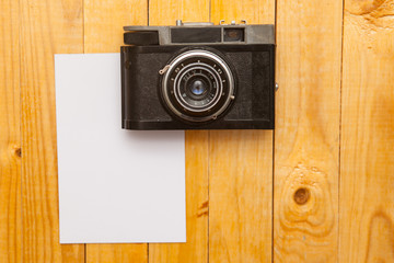 old camera with a photo on a wooden background