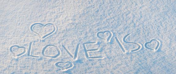 Word LOVE IS on snow