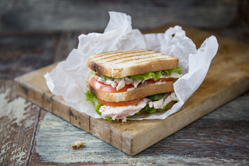 Chicken Club Sandwich with Lettuce and Tomato on old wooden