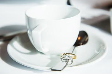 Cup of coffee, wedding rings in spoon on table