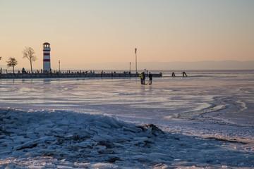 Leuchtturm in zartem Abendrot hinter Eisschollen und gefrorenem See