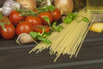 Preparing homemade pasta. Pasta and vegetables on a wooden table. Dietary food. Pasta, tomatoes, onion, olive oil and basil on wooden background.