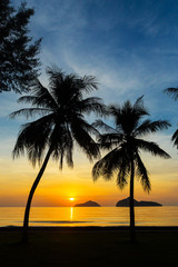 Sunrise at sea with islands and coconut trees.