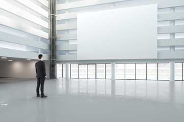 man looking at a blank white banner in a large bright hall, mock