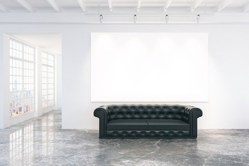 Blank white poster on white wall with black leather sofa on conc