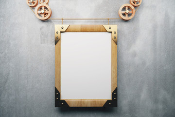 Blank wooden picture frame steampunk style on grey concrete wall