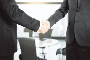 Handshake of two businessmen in a conference room