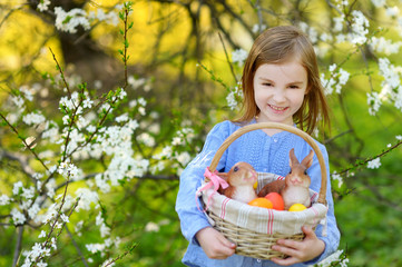Adorable little girl holding a basket of Easter eggs on Easter day