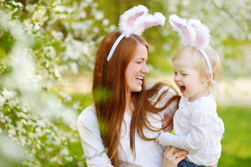 Young mother and her daughter wearing bunny ears on Easter day