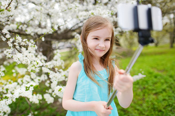 Adorable little girl taking a photo of herself with a selfie stick