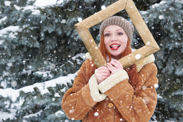 Woman outdoor portrait in wooden photo frame at winter season. Snowy weather in fir tree park.