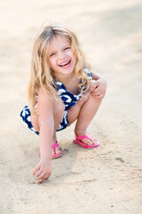 Beautiful laughing little girl with long blond hair squatting and drawing in the sand on the beach in summer day