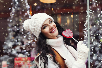 Street portrait of smiling beautiful young woman holding candy heart. Lady wearing classic winter knitted clothes. Model looking at camera. Festive background. Magic snowfall effect. Close up.
