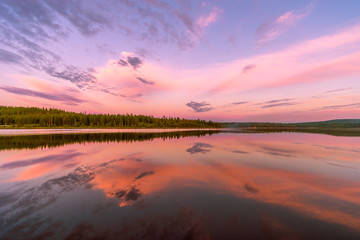 Summer landscape with river, forest and cloudy sky and reflection and sunset