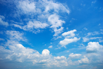 Blue sky with clouds on a summer day .