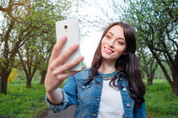 Youth and technology. Young smiling woman taking selfie by smart