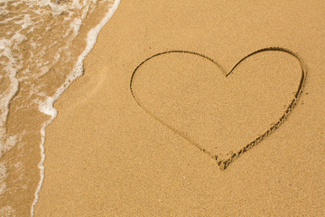 Heart drawn on the beach sand with a soft wave.