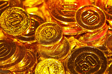 Golden coins piled in a heap of background