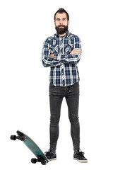 Confident bearded hipster wearing plaid tartan shirt posing with his skateboard. Full body length portrait isolated over white studio background.