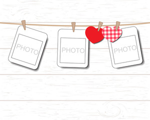 Blank instant photo and small red paper heart hanging on the clothesline