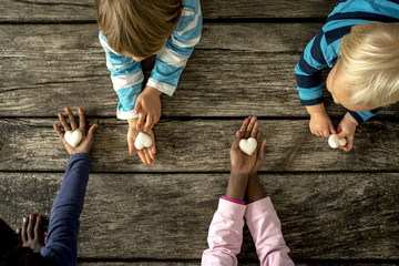 Top view of four children of mixed races each holding a marble h
