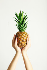Female hands holding ripe pineapple on a white background