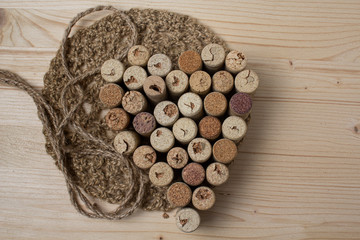 Heart laid out from bottle corks on wooden background