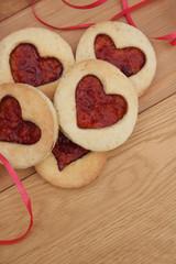 biscotti  a forma di cuore con marmellata su tavolo di legno.  San Valentino