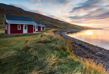 Red cottage seaside with plant foreground and mountain range background during sunrise time at Eskifjorour Iceland in Autumn season