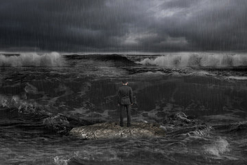 businessman standing on rock facing oncoming waves with dark oce