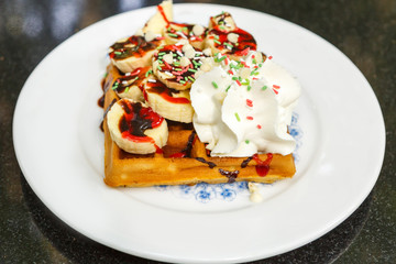 Waffle with banana slices and cream