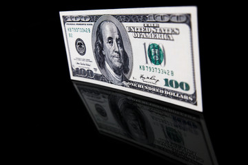 Close up of used hundred dollar banknote on black background with reflection