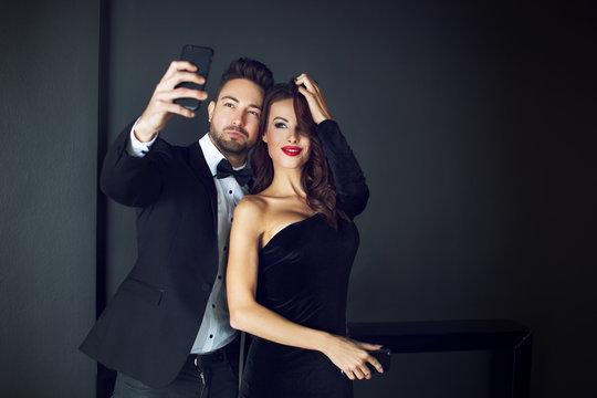 Fashionable rich celebrity couple taking selfie