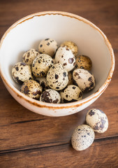 Quail eggs in a bowl on a wooden rustic table, selective focus
