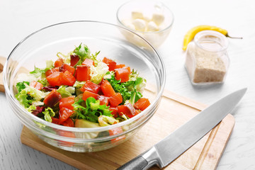 Tasty salad in glass dish on color wooden table background