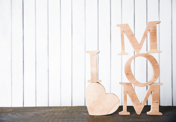 I love mom inscription of wooden letters with heart on white wall background