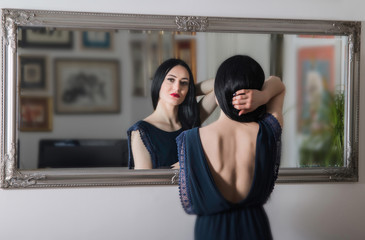 Portrait of beautiful young woman in blue dress with naked back, standing in front of the mirror, beauty fashion concept, blurred background