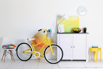 Yellow bicycle with books in light living room interior