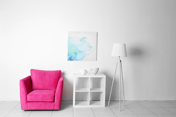 Living room interior with pink armchair, white shelf and lamp  on white wall background